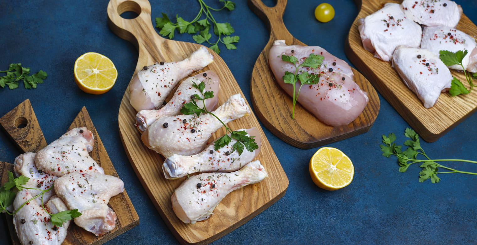 Raw chicken meat fillet, thigh, wings and legs with herbs ,spices,lemon and garlic on dark blue background. Top view